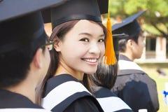 Kvinna som står ut från le för avläggande av examengrupp Arkivbild