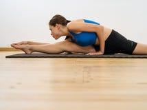Kvinna som sträcker henne ben i idrottshallen Arkivfoton