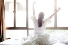 Kvinna som sträcker i säng efter vak upp Arkivfoto