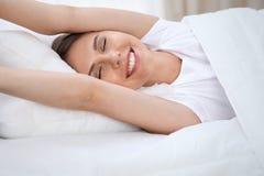 Kvinna som sträcker i säng efter vak upp och att skriva in en avkopplad dag som är lycklig och efter sömn för bra natt Söta drömm arkivfoton