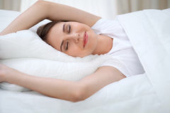 Kvinna som sträcker i säng efter vak upp och att skriva in en avkopplad dag som är lycklig och efter sömn för bra natt Söta drömm royaltyfri fotografi
