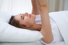 Kvinna som sträcker i säng efter vak upp och att skriva in en avkopplad dag som är lycklig och efter sömn för bra natt Söta drömm royaltyfri foto