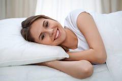 Kvinna som sträcker i säng efter vak upp och att skriva in en avkopplad dag som är lycklig och efter sömn för bra natt Söta drömm arkivfoto