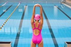 Kvinna som sträcker och förbereder sig till att simma Arkivbild