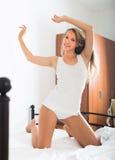 Kvinna som sträcker på säng på sovrummet Fotografering för Bildbyråer