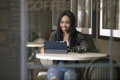 Kvinna som strömmar video på en minnestavla i en Coffeeshop Arkivfoton