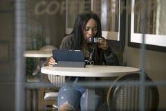 Kvinna som strömmar video på en minnestavla i en Coffeeshop Royaltyfri Foto