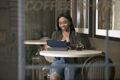 Kvinna som strömmar video på en minnestavla i en Coffeeshop Arkivfoto