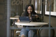 Kvinna som strömmar video på en minnestavla i en Coffeeshop Royaltyfria Foton