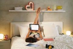 Kvinna som studerar i säng som gör läxa på solnedgången Arkivbild