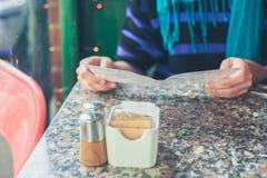 Kvinna som studerar menyn i ett kafé Arkivfoto
