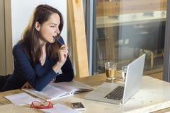 Kvinna som studerar sammanträde som ser hennes bärbar dator som har att tänka för kaffe Royaltyfria Bilder