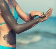 Kvinna som suddar gyttjamaskeringen på kroppen Arkivfoton