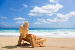 Kvinna som suntanning på stranden i Grekland Arkivfoto