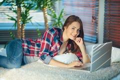 Kvinna som surfar det netto på soffan Fotografering för Bildbyråer