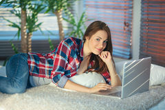 Kvinna som surfar det netto på soffan Royaltyfria Bilder