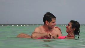 Kvinna som svävar i vatten med mannen lager videofilmer