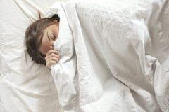 Kvinna som täckas med kudden. Sova i en vit säng. Royaltyfri Bild