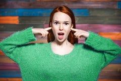 Kvinna som täcker henne öron med ditt fingrar och ropa Arkivfoton
