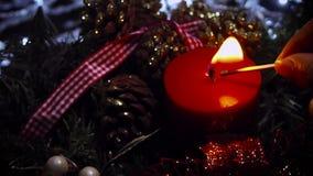 Kvinna som tänder en röd julljus stock video