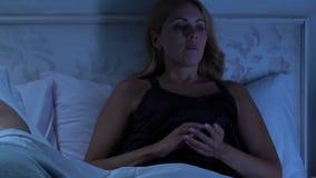 Kvinna som tänker över problem som ligger i säng medan make som sover i stillhet bredvid lager videofilmer
