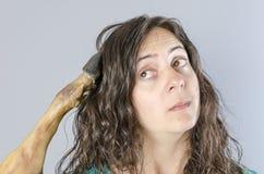 Kvinna som tänker med skinkabenet i hennes huvud Dumt läge arkivfoto