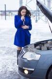 Kvinna som tänker och ser under huven av en bil Arkivfoto