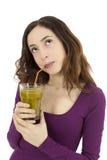 Kvinna som tänker och ser upp med ett smoothieexponeringsglas i hennes hand royaltyfria bilder