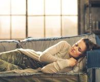 Kvinna som ta sig en tupplur på en soffa i en stadsvind royaltyfri bild