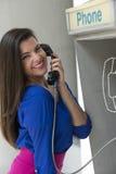 Kvinna som talar i offentlig telefon Royaltyfri Bild