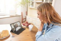Kvinna som talar med mannen till och med en video pratstund royaltyfri foto