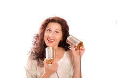 Kvinna som talar och hör till och med tenn- telefoner Royaltyfria Bilder
