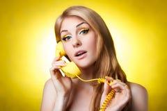 Kvinna som talar på den gula telefonen Fotografering för Bildbyråer