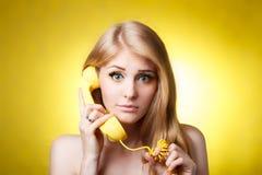 Kvinna som talar på den gula telefonen Royaltyfria Foton