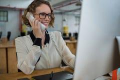 Kvinna som talar på landlinetelefonen på skrivbordet royaltyfria bilder