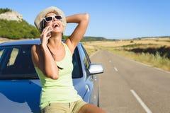 Kvinna som talar på mobiltelefonen under sommarbillopp Arkivfoton