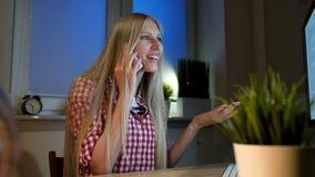Kvinna som talar på smartphonen i mörkt rum Härligt le blont kvinnligt sammanträde på träskrivbordet med datoren på natten arkivfilmer