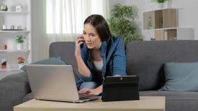 Kvinna som talar på telefonen genom att använda åtskilliga apparater arkivfilmer