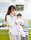 Kvinna som talar på telefonen, medan rymma henne behandla som ett barn i hennes armar Fotografering för Bildbyråer