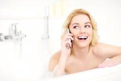 Kvinna som talar på telefonen, när ta ett bad Royaltyfri Fotografi