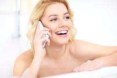 Kvinna som talar på telefonen, när ta ett bad Arkivfoto