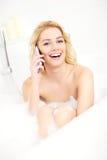 Kvinna som talar på telefonen, när ta ett bad Fotografering för Bildbyråer