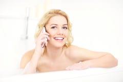 Kvinna som talar på telefonen, när ta ett bad Arkivfoton