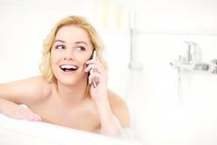 Kvinna som talar på telefonen, när ta ett bad Royaltyfri Foto