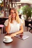Kvinna som talar på telefonen och använder minnestavlan arkivfoton