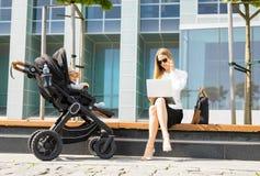 Kvinna som talar på telefonen och arbetet på bärbar datoroutdors, medan ha en behandla som ett barn i sittvagn Arkivfoton