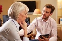 Kvinna som talar till den manliga rådgivaren som använder den Digital fliken royaltyfria foton