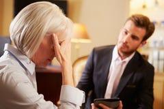 Kvinna som talar till den manliga rådgivaren som använder den Digital fliken royaltyfri foto