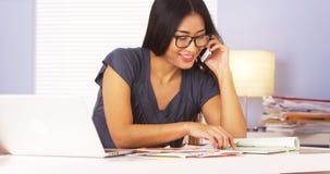 Kvinna som talar till hennes bank med smartphonen arkivbild