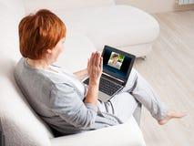 Kvinna som talar till hennes moder på datoren Arkivfoto